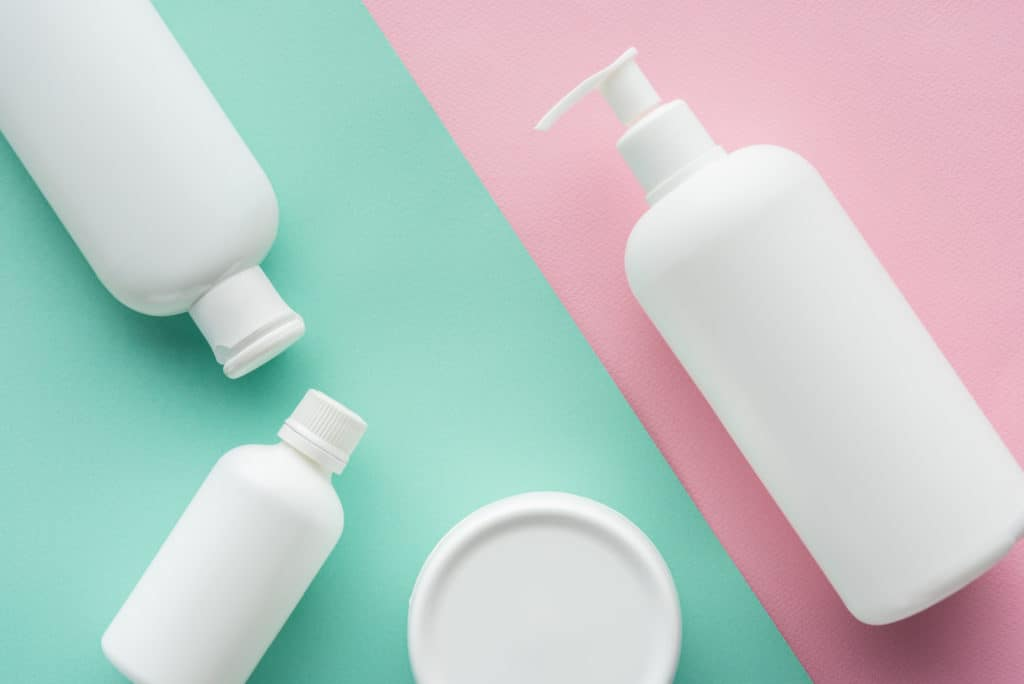 Top view of moisturizer bottles on green and pink surface