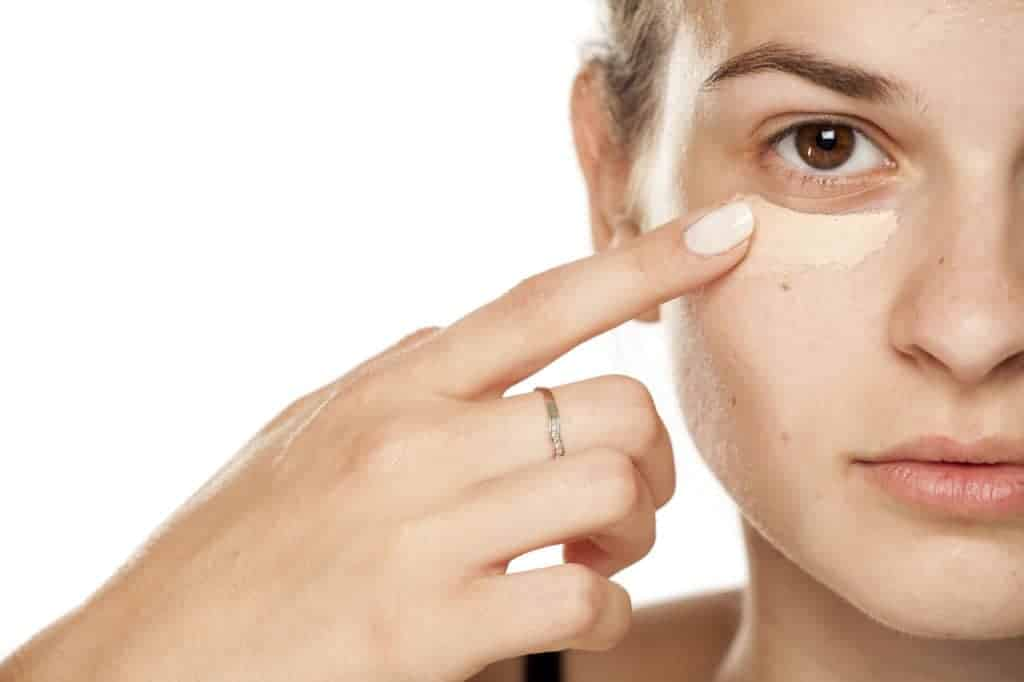 Young woman applying concealer under her eyes