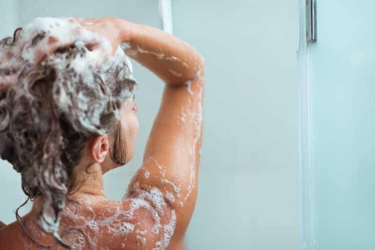 Woman applying shampoo in shower