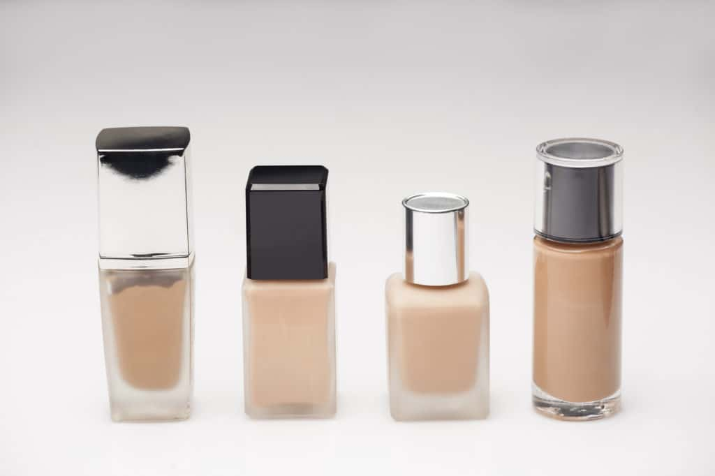 different bottles with liquid foundation on white background