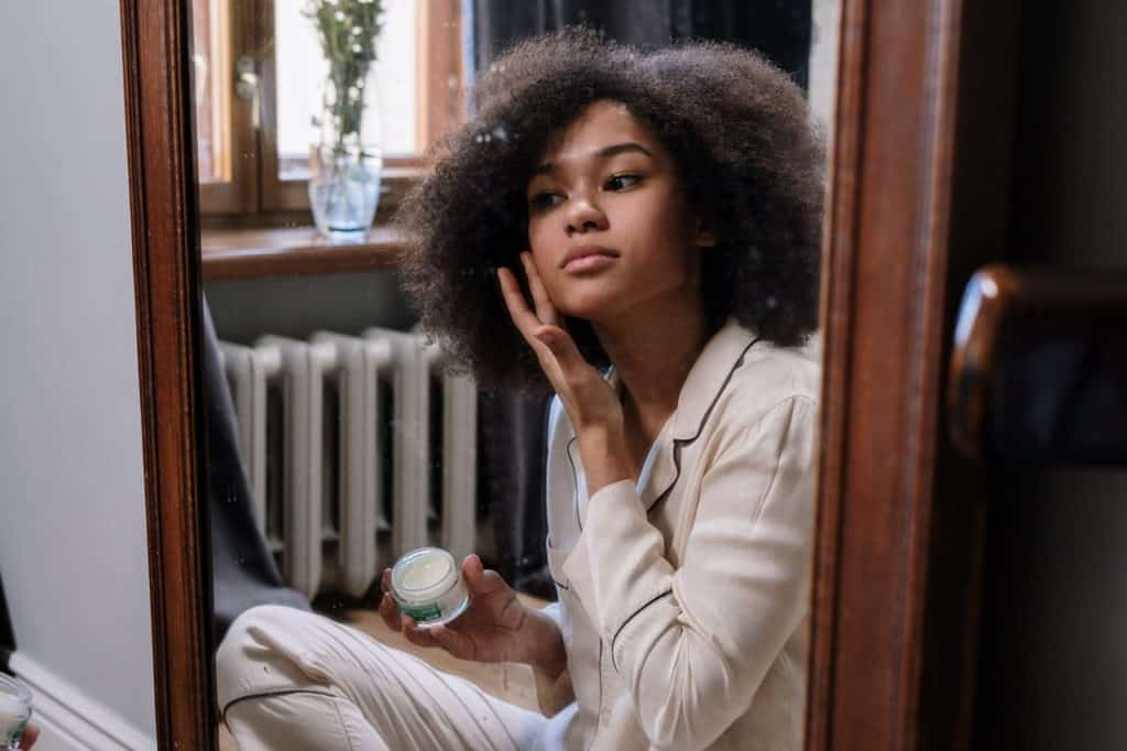 woman sitting in front of a mirror applying face cream