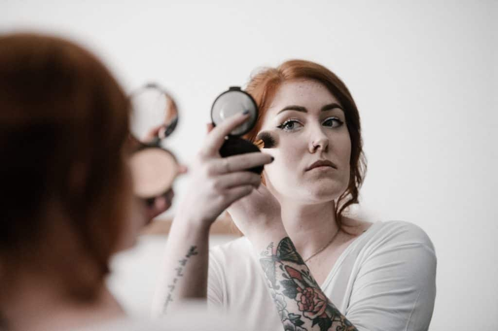 woman applying powder foundation while looking in a mirror