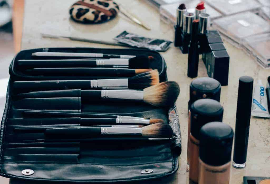liquid foundations and a bag with makeup brushes on a table