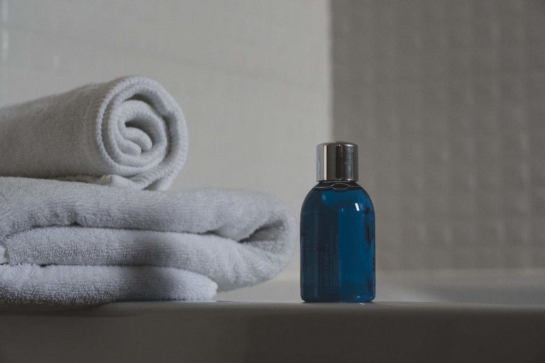 a blue bottle next to some towels on a bathtub counter