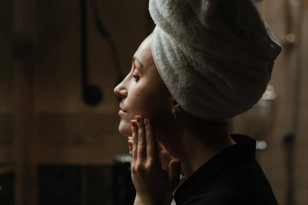 woman in black shirt patting her skin and covering her hair with gray towel