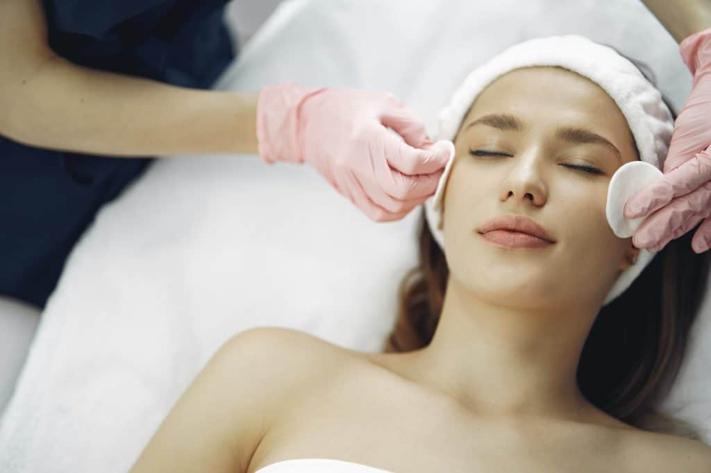 woman laying down getting a facial where someone applies toner with cotton pads